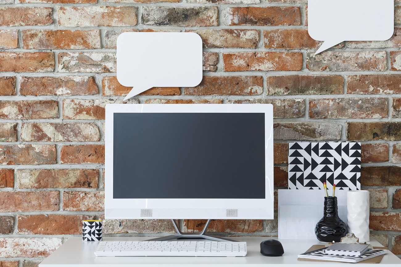Modern desk with computer against brick wall with mockup speech bubbles